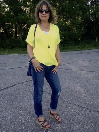 Wie kombinieren: gelbes T-Shirt mit einem V-Ausschnitt, blaue Boyfriend Jeans mit Destroyed-Effekten, braune Keilsandaletten aus Leder, blaue Leder Umhängetasche