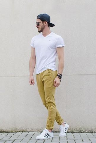 Wie kombinieren: weißes T-Shirt mit einem V-Ausschnitt, senf Chinohose, weiße Leder niedrige Sneakers, schwarze Baseballkappe