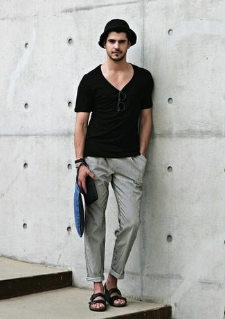 schwarzes T-Shirt mit einem V-Ausschnitt, graue Chinohose, schwarze Ledersandalen, schwarzer Strohhut für Herren