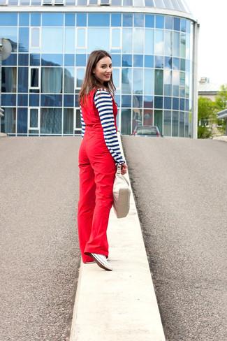 Wie kombinieren: dunkelblaues und weißes horizontal gestreiftes T-shirt mit einer Knopfleiste, rote Latzhose, weiße Segeltuch niedrige Sneakers, hellbeige Lederhandtasche