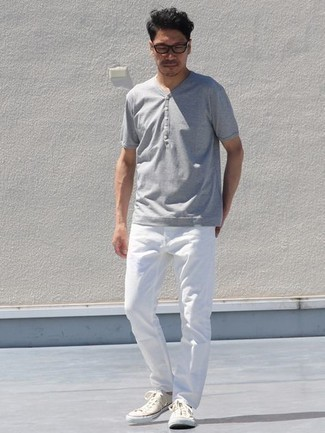 Graues T-shirt mit einer Knopfleiste kombinieren – 86 Herren Outfits: Tragen Sie ein graues T-shirt mit einer Knopfleiste und weißen Jeans für ein bequemes Outfit, das außerdem gut zusammen passt. Komplettieren Sie Ihr Outfit mit hellbeige Segeltuch niedrigen Sneakers.