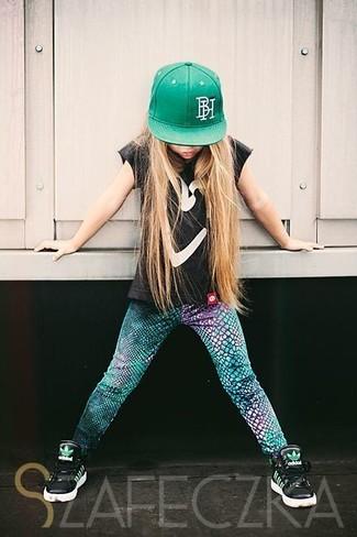 Wie kombinieren: schwarzes T-shirt, grüne Leggings, schwarze Turnschuhe, grüne Baseballkappe