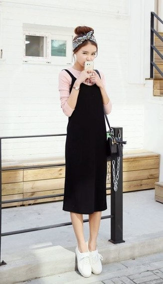 Wie kombinieren: schwarzes Trägerkleid, rosa Langarmshirt, weiße Leder niedrige Sneakers, schwarze Leder Umhängetasche