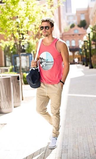 Wie kombinieren: rosa bedrucktes Trägershirt, hellbeige Jogginghose, weiße Leinenschuhe, schwarze und weiße Segeltuch Sporttasche