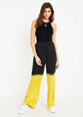 Wie kombinieren: schwarzes Trägershirt, gelbe Mit Batikmuster weite Hose, weiße Sportschuhe, goldener Anhänger