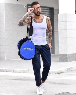 Wie kombinieren: weißes Trägershirt, dunkelblaue Jogginghose, weiße niedrige Sneakers, blaue Sporttasche