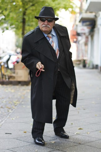 Wie kombinieren: schwarzer Trenchcoat, schwarzer vertikal gestreifter Anzug, hellblaues Businesshemd, schwarze Chelsea-Stiefel aus Leder