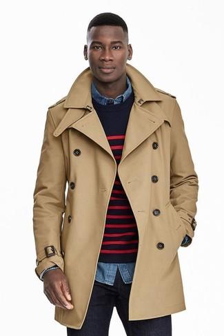 Wie kombinieren: beige Trenchcoat, dunkelblauer und roter horizontal gestreifter Pullover mit einem Rundhalsausschnitt, blaues Jeanshemd, dunkelblaue Jeans