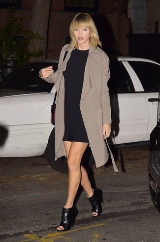 Taylor Swift trägt Brauner Trenchcoat, Schwarzes Gerade Geschnittenes Kleid, Schwarze Leder Stiefeletten mit Ausschnitten, Schwarze Leder Umhängetasche