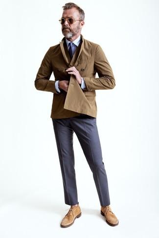 Lalle Johnson trägt brauner Trenchcoat, weißes Businesshemd, graue Anzughose, beige Chukka-Stiefel aus Wildleder