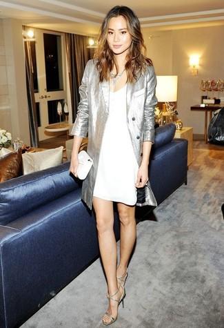 Wie kombinieren: silberner Trenchcoat, weißes Camisole-Kleid, silberne Leder Sandaletten, weiße Leder Clutch