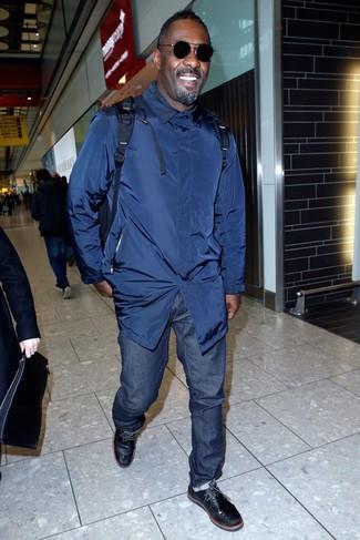 Idris Elba trägt Dunkelblauer Trenchcoat, Dunkelblaue Jeans, Schwarze Chukka-Stiefel aus Leder, Dunkelblauer Rucksack