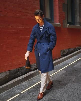 Wie kombinieren: dunkelblauer Trenchcoat, weißes und dunkelblaues horizontal gestreiftes T-Shirt mit einem Rundhalsausschnitt, hellbeige Leinen Anzughose, braune Leder Slipper