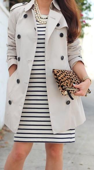 Entscheiden Sie sich für einen hellbeige Trenchcoat und ein schwarzes und weißes horizontal gestreiftes Etuikleid für einen für die Arbeit geeigneten Look.
