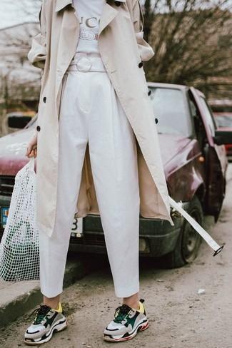 Wie kombinieren: hellbeige Trenchcoat, weißes bedrucktes T-Shirt mit einem Rundhalsausschnitt, weiße Karottenhose, graue Sportschuhe
