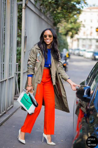 Wie kombinieren: olivgrüner Trenchcoat, blauer kurzer Pullover, rote weite Hose, weiße Leder Pumps