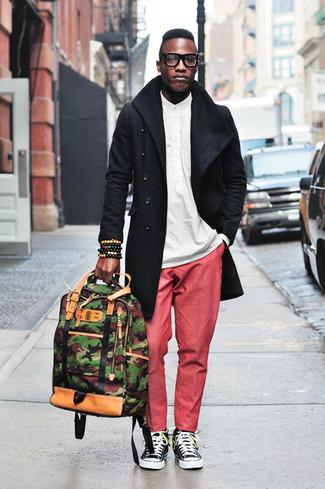 Wie kombinieren: schwarzer Trenchcoat, weißes Langarmhemd, rote Chinohose, schwarze und weiße Segeltuch niedrige Sneakers