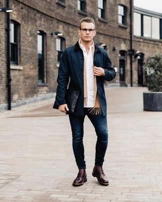 Wie kombinieren: dunkelblauer Trenchcoat, weißes Langarmhemd, dunkelblaue enge Jeans, dunkelrote Leder Brogues