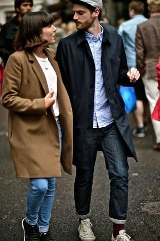 Wie kombinieren: schwarzer Trenchcoat, hellblaues Langarmhemd, dunkelblaue Jeans, weiße Segeltuch niedrige Sneakers