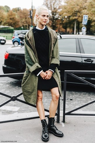 Wie kombinieren: olivgrüner Trenchcoat, schwarzes Sweatkleid, weißes Businesshemd, schwarze flache Stiefel mit einer Schnürung aus Leder