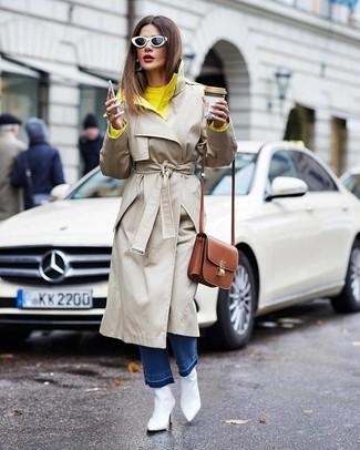 Wie kombinieren: hellbeige Trenchcoat, gelber Pullover mit einem Rundhalsausschnitt, blaue Jeans, weiße Leder Stiefeletten