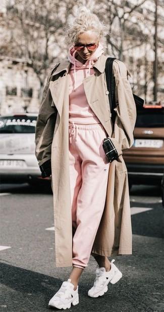 Wie kombinieren: hellbeige Trenchcoat, rosa Pullover mit einer Kapuze, rosa Jogginghose, weiße Sportschuhe