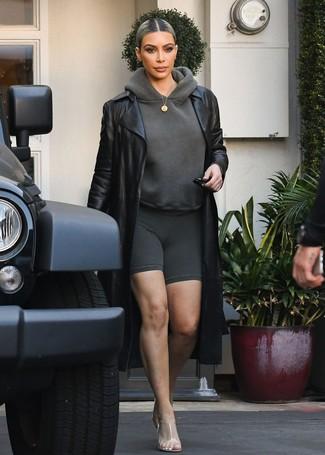Wie kombinieren: schwarzer Leder Trenchcoat, dunkelgrauer Pullover mit einer Kapuze, dunkelgraue Radlerhose, transparente Gummi Pantoletten