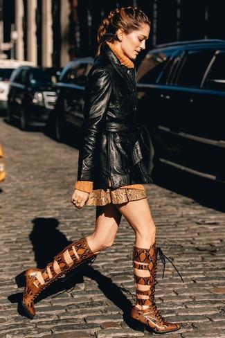 Wie kombinieren: schwarzer Leder Trenchcoat, orange Strick Rollkragenpullover, brauner Leder Minirock mit Schlangenmuster, rotbraune kniehohe Stiefel aus Leder mit Schlangenmuster