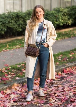 Wie kombinieren: hellbeige Trenchcoat, weißes und dunkelblaues horizontal gestreiftes T-Shirt mit einem Rundhalsausschnitt, dunkelblaue Jeans, weiße Segeltuch niedrige Sneakers