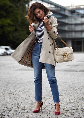 Wie kombinieren: hellbeige Trenchcoat, weißes und schwarzes horizontal gestreiftes T-Shirt mit einem Rundhalsausschnitt, blaue Jeans, dunkelrote Wildleder Pumps