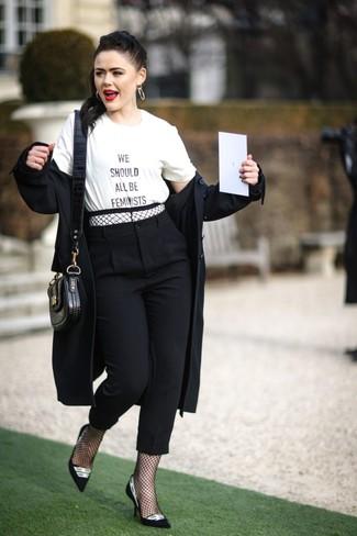 Wie kombinieren: schwarzer Trenchcoat, weißes und schwarzes bedrucktes T-Shirt mit einem Rundhalsausschnitt, schwarze Karottenhose, schwarze und weiße Wildleder Pumps