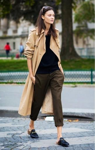 Wie kombinieren: beige Trenchcoat, schwarzes T-Shirt mit einem Rundhalsausschnitt, dunkelbraune Karottenhose, schwarze Leder Slipper