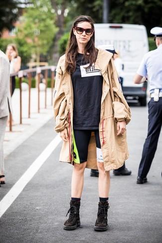 Wie kombinieren: beige Trenchcoat, schwarzes und weißes bedrucktes T-Shirt mit einem Rundhalsausschnitt, schwarze bedruckte Radlerhose, dunkelbraune flache Stiefel mit einer Schnürung aus Wildleder