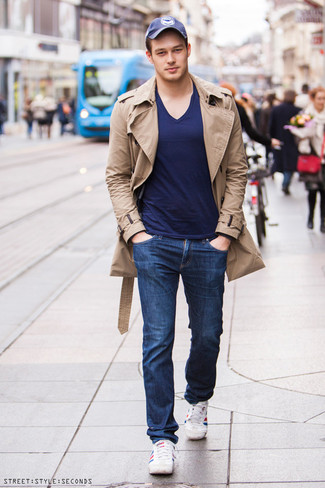 Wie kombinieren: beige Trenchcoat, dunkelblaues T-Shirt mit einem V-Ausschnitt, dunkelblaue Jeans, weiße und rote und dunkelblaue horizontal gestreifte niedrige Sneakers