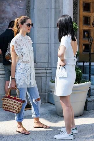 Wie kombinieren: weiße Spitzetunika, hellblaue Boyfriend Jeans mit Destroyed-Effekten, dunkelbraune verzierte flache Sandalen aus Leder, beige Strohhandtasche