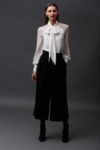 Diese Kombination aus einer weißen Langarmbluse und einem schwarzen Hosenrock bietet die perfekte Balance zwischen einem Freizeit-Look und modischem Stil. Schwarze leder stiefeletten mit ausschnitten fügen sich nahtlos in einer Vielzahl von Outfits ein.