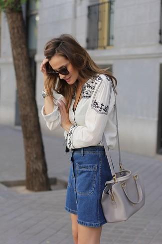 Wie kombinieren: weiße und schwarze bestickte Folklore Bluse, blauer Jeansrock mit knöpfen, graue Leder Umhängetasche