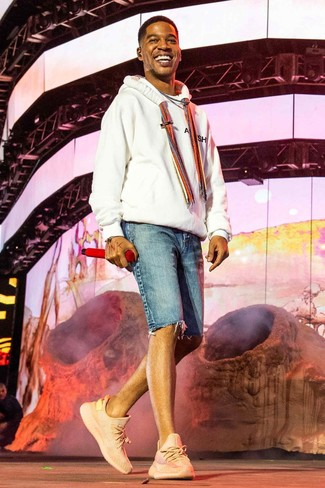Kid Cudi trägt weißer Pullover mit einem Kapuze, blaue Jeansshorts, rosa Sportschuhe