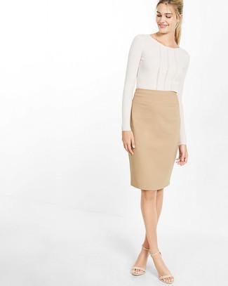 Beige Bleistiftrock kombinieren – 11 Damen Outfits: Wahlen Sie einen weißen Pullover mit einem Rundhalsausschnitt und einen beige Bleistiftrock, um sich selbstbewusst zu fühlen und modisch auszusehen. Hellbeige Leder Sandaletten sind eine perfekte Wahl, um dieses Outfit zu vervollständigen.