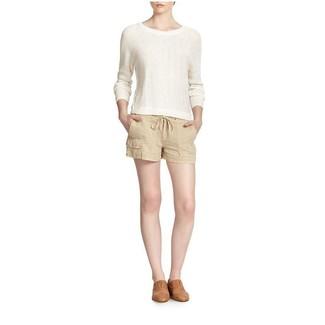 Wie kombinieren: weißer Pullover mit einem Rundhalsausschnitt, hellbeige Leinen Shorts, beige Leder Slipper