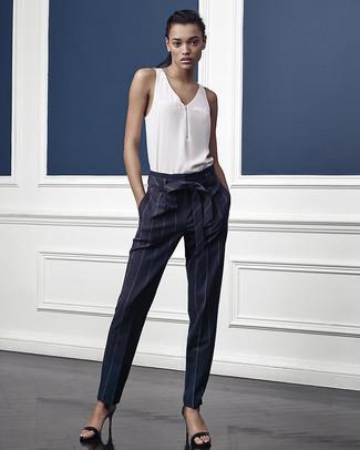 Wie kombinieren: weißes ärmelloses Oberteil aus Seide, dunkelblaue vertikal gestreifte Karottenhose, schwarze Leder Sandaletten