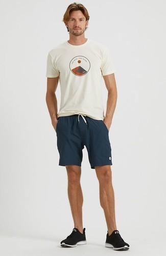 Herren Outfits 2020: Ein weißes bedrucktes T-Shirt mit einem Rundhalsausschnitt und dunkelblaue Sportshorts sind eine ideale Outfit-Formel für Ihre Sammlung. Schwarze und weiße Sportschuhe sind eine ideale Wahl, um dieses Outfit zu vervollständigen.