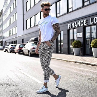 Wie kombinieren: weißes bedrucktes T-Shirt mit einem Rundhalsausschnitt, weiße und schwarze Chinohose mit Karomuster, weiße Leder niedrige Sneakers