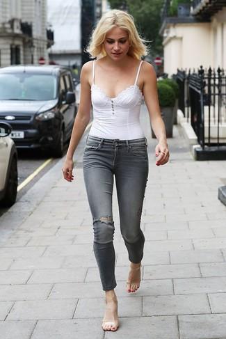 Transparente Gummi Sandaletten kombinieren – 18 Damen Outfits: Diese Paarung aus einem weißen Bustier-Oberteil und grauen engen Jeans mit Destroyed-Effekten ist eine ideale Option füreinen entspannten Look. Vervollständigen Sie Ihr Look mit transparenten Gummi Sandaletten.