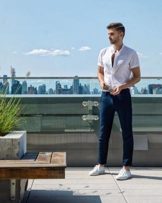 Wie kombinieren: weißes Kurzarmhemd, dunkelblaue Chinohose, weiße niedrige Sneakers