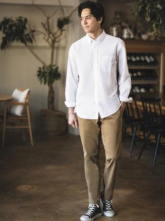 Wie kombinieren: weißes Langarmhemd, beige Chinohose, schwarze und weiße hohe Sneakers aus Segeltuch
