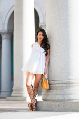 Wie kombinieren: weißes schwingendes Kleid mit Rüschen, braune hohe Römersandalen aus Leder, senf Lederhandtasche