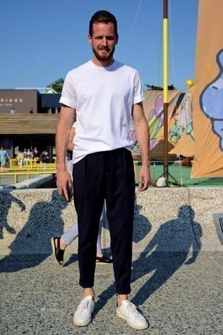 Dunkelblaue Chinohose kombinieren: trends 2020: Tragen Sie ein weißes T-Shirt mit einem Rundhalsausschnitt und eine dunkelblaue Chinohose für ein großartiges Wochenend-Outfit. Ergänzen Sie Ihr Look mit weißen Leder niedrigen Sneakers.