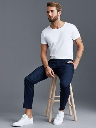 Weißes T-Shirt mit einem Rundhalsausschnitt kombinieren – 1200+ Herren Outfits: Kombinieren Sie ein weißes T-Shirt mit einem Rundhalsausschnitt mit einer dunkelblauen Chinohose für ein Alltagsoutfit, das Charakter und Persönlichkeit ausstrahlt. Weiße Segeltuch niedrige Sneakers sind eine großartige Wahl, um dieses Outfit zu vervollständigen.
