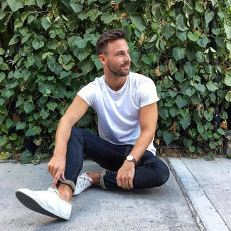 Wie kombinieren: weißes T-Shirt mit einem Rundhalsausschnitt, dunkelblaue enge Jeans, weiße Segeltuch niedrige Sneakers